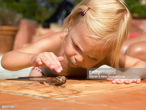 little girl playing with a snail. - limace photos et images de collection