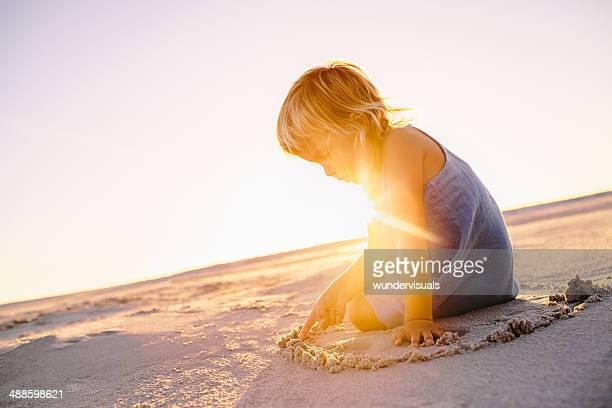 Petite fille jouant avec le sable sur la plage