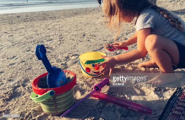 Little girl playing with beach toys on the Mediterranean beach