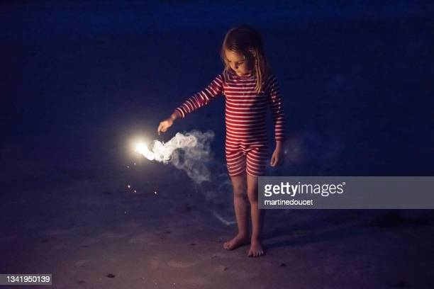 """little girl playing with bengal fire on the beach at dusk. - """"martine doucet"""" or martinedoucet stock pictures, royalty-free photos & images"""