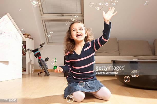 Kleines Mädchen spielen mit Blasen