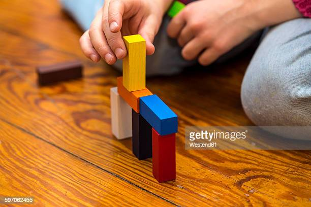 Little girl playing with building bricks on wooden floor, close-up