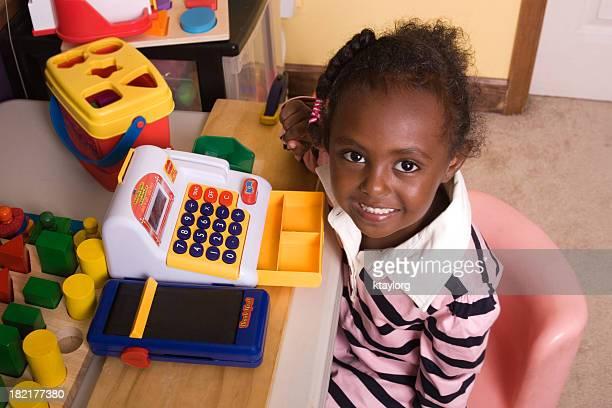 Kleines Mädchen spielt mit cash register