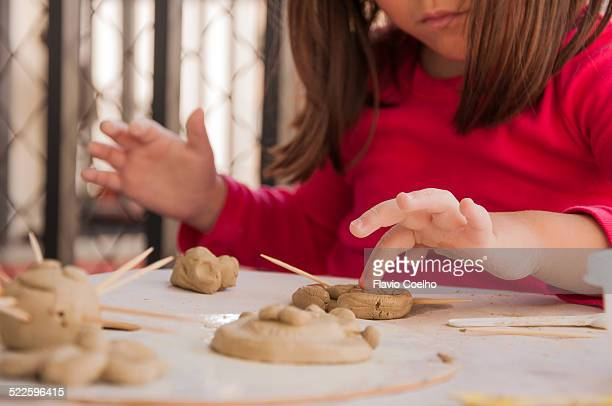 Little girl playing with clay