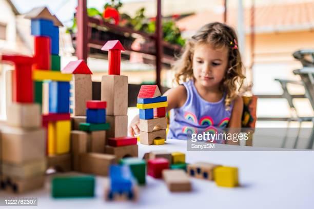 meisje dat met kleurrijke bouwstenen speelt - blokken stockfoto's en -beelden