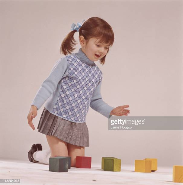 A little girl playing with coloured wooden building blocks circa 1965