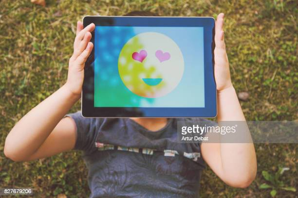Little girl playing with digital tablet and colorful emoticon displayed on the screen taken from above