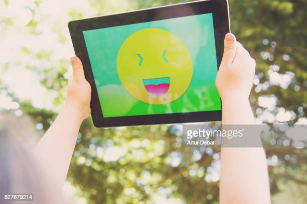 Little girl playing with digital tablet and colorful emoticon displayed on the screen from personal perspective.
