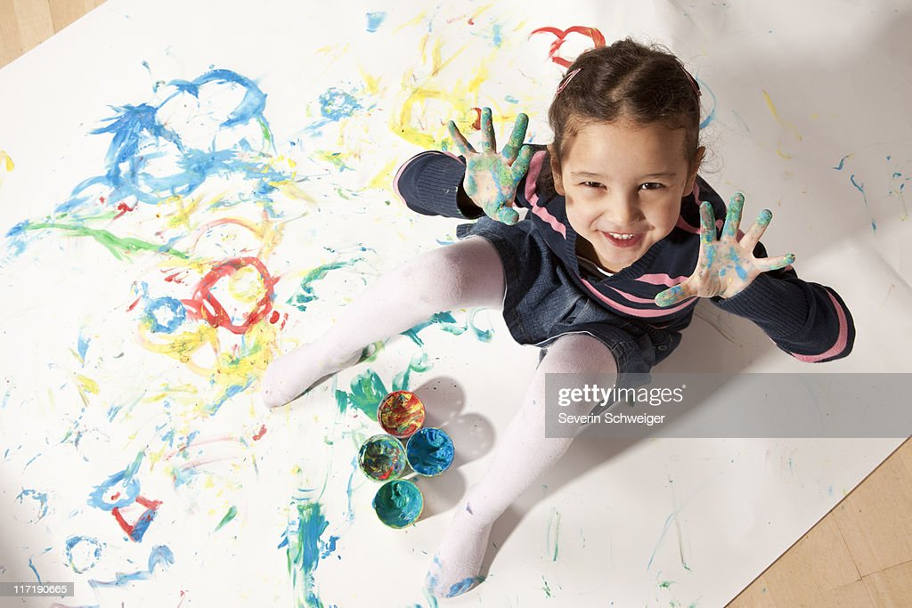 Little girl playing with finger paint : Stock Photo