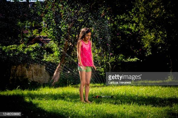 little girl playing with garden sprinkler - larissa veronesi stock-fotos und bilder