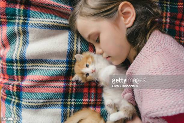 Little girl playing with kitten on the bed