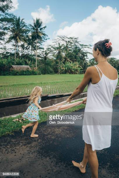 petite fille jouant avec mère près de rizière à bali - petite fille culotte photos et images de collection