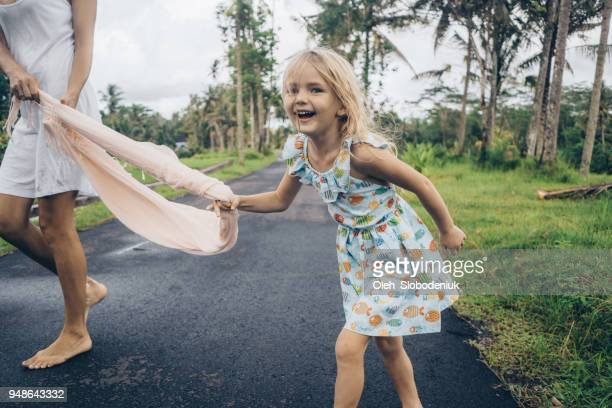 Little  girl playing with mother near rice field in Bali