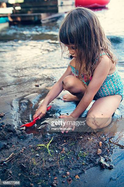 Little girl playing with mud in lake water.