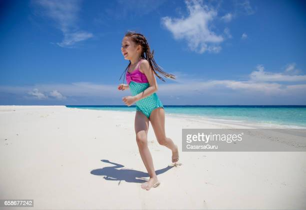 Little Girl Playing With Own Shadow On The Tropical Beach