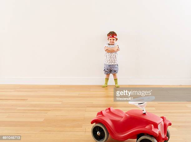 Little girl playing with pedal car