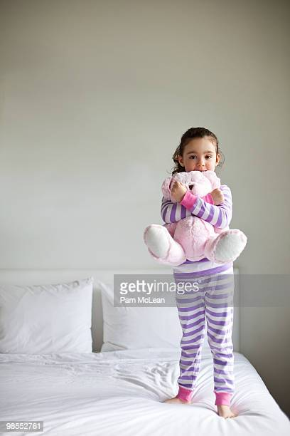 Little girl playing with pink teddy bear