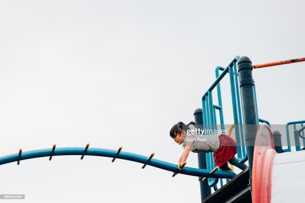 Little girl playing with playground equipment : Stock Photo