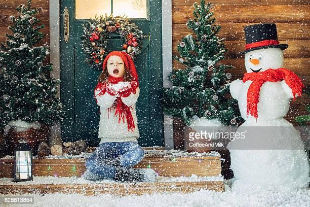 Kleine Mädchen spielen mit Schnee