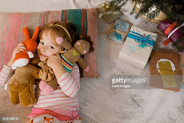 Little girl playing with stuffed animals alongside Christmas tree, Munich, Bavaria, Germany