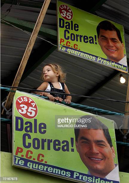 A little girl plays next to propaganda of presidential candidate Rafael Correa 14 October in the town of Recreo Guayas province Ecuador Leftist US...