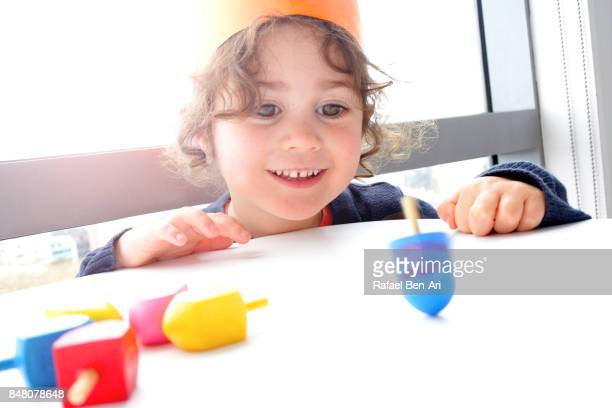 little girl plays with dreidels on hanukkah jewish holiday - dreidel stock photos and pictures