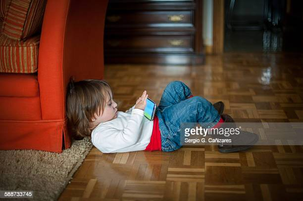 Little girl plays with smartphone at home