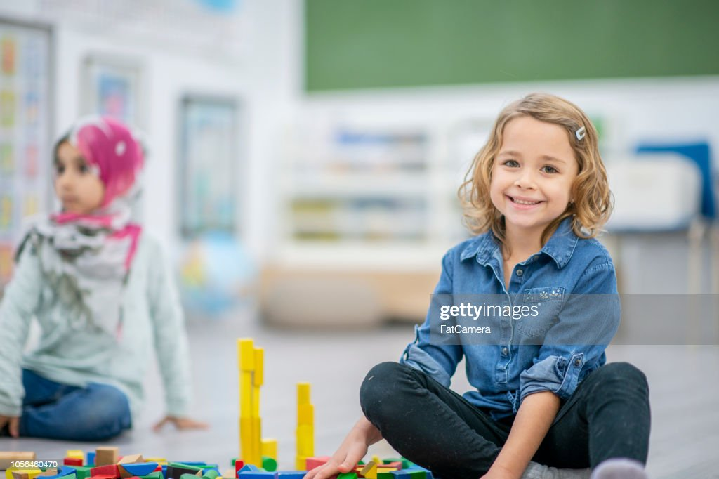Little girl plays with toys while sitting on the ground : Stock Photo