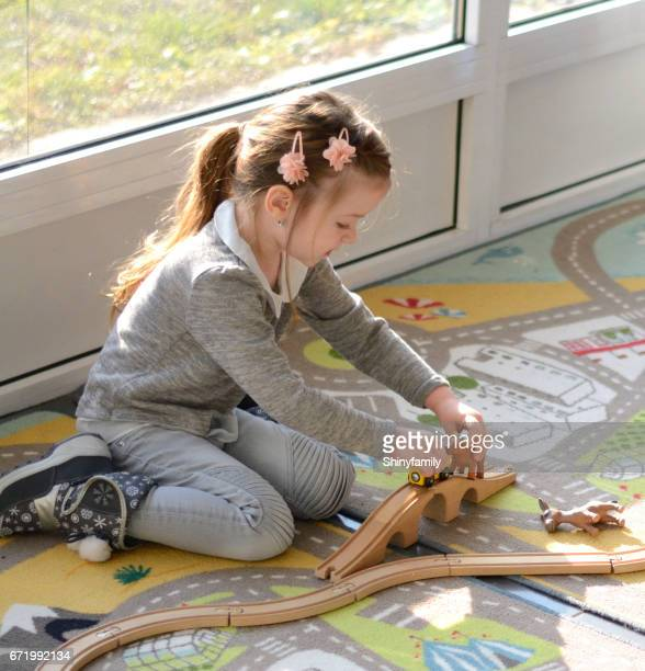 Little girl plays with toys, wooden train, railway and animals