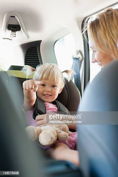Little girl pointing and smiling as her mother fastens her into car seat
