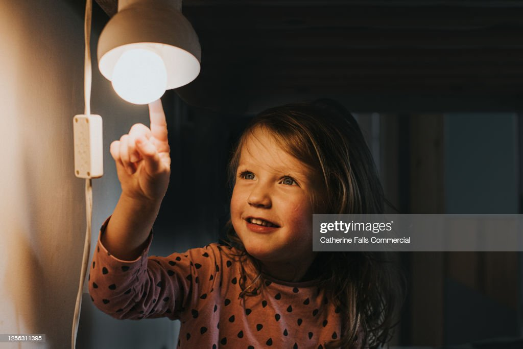 Little girl pointing at a Light : Stock Photo