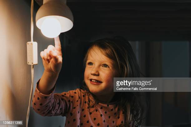 little girl pointing at a light - イルミネーション ストックフォトと画像