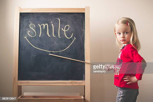 Little girl pointing at the word smile on a blackboard