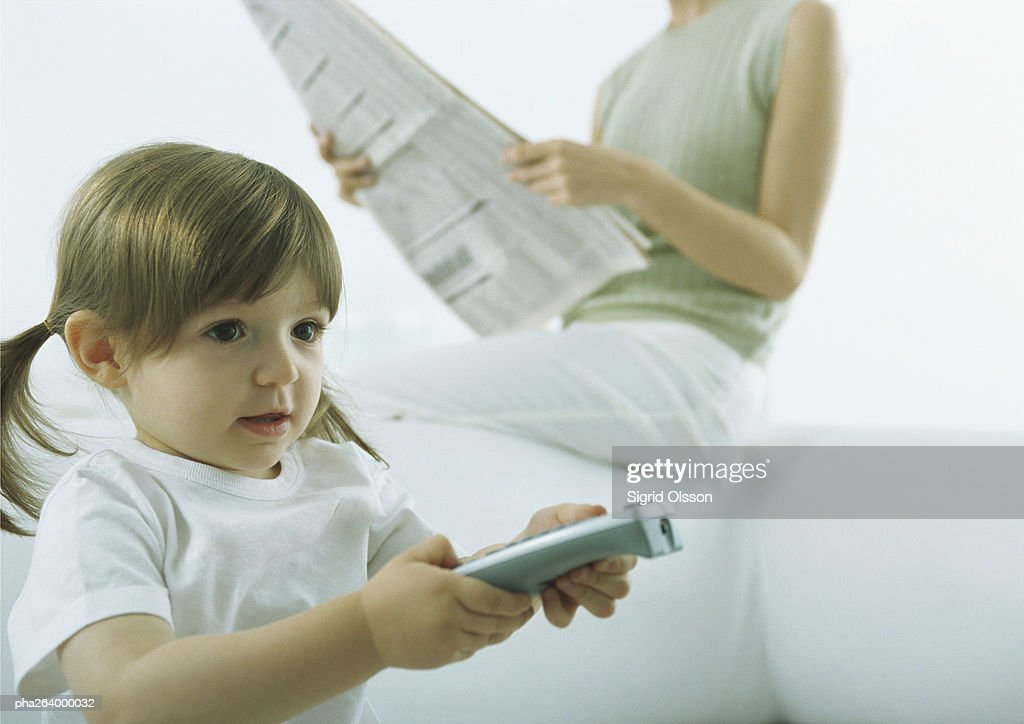 Little girl pointing remote control, woman sitting on back of sofa holding newspaper in background : Stockfoto