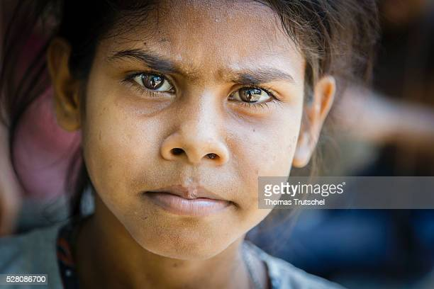 A little girl poses for a photo on the market on April 11 2016 in Khulna Bangladesh