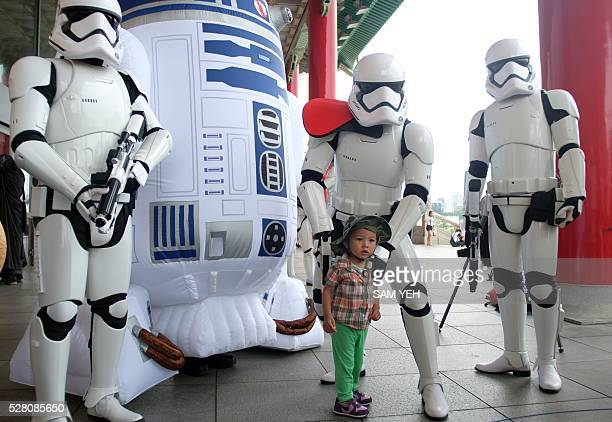 A little girl poses for a photo with Star Wars fans during the annual Star Wars Day in Taipei on May 4 2016 Some 100 star wars fans dress the...