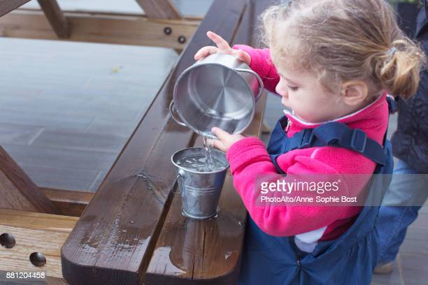 Little girl pouring water from one pail to another