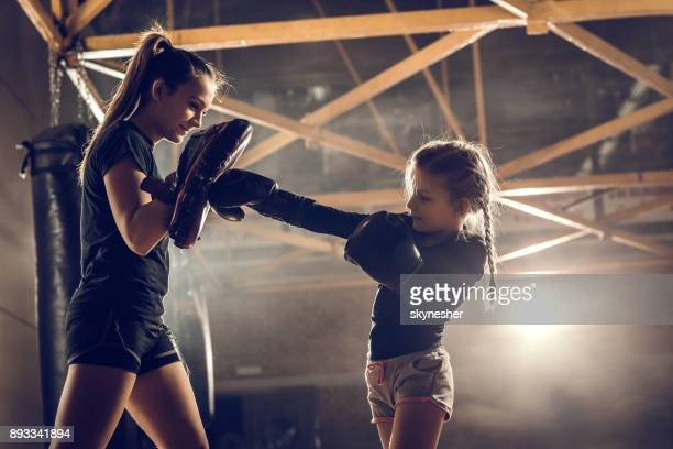 little girl practicing boxing with her coach in health club. - boxing stock pictures, royalty-free photos & images