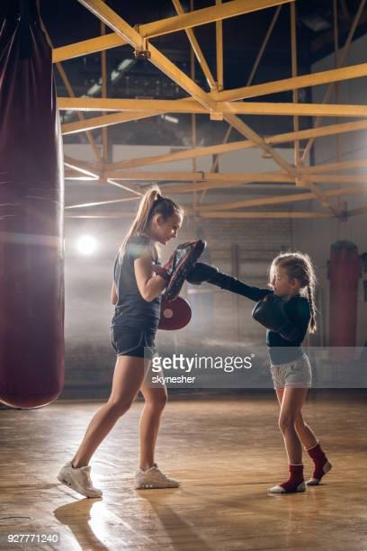 Kleines Mädchen üben Boxen mit ihrem Trainer im Fitnessstudio.
