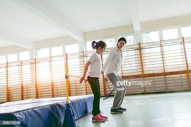 Little Girl Practicing High Jump With Her Instructor.
