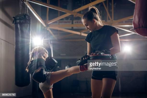 menina praticando kickboxing com seu técnico no clube de saúde. - chutar - fotografias e filmes do acervo
