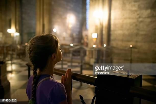 Little girl praying at the church