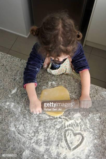 little girl prepares dough - rafael ben ari stock-fotos und bilder