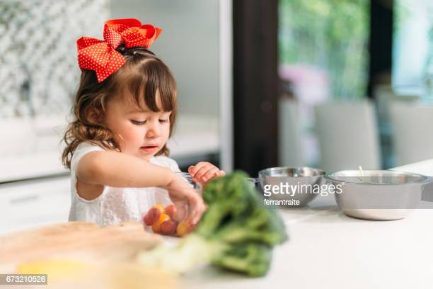 Little girl preparing a salad