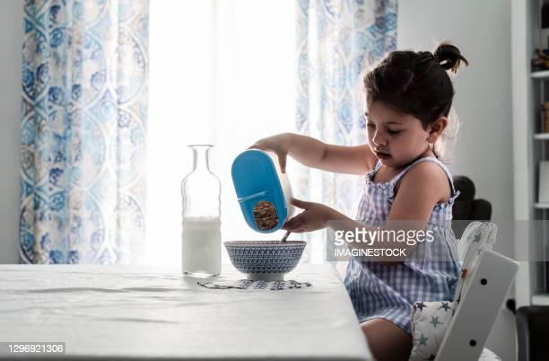 little girl preparing the cereal-milk breakfast in the dining room at home - chairperson stock pictures, royalty-free photos & images
