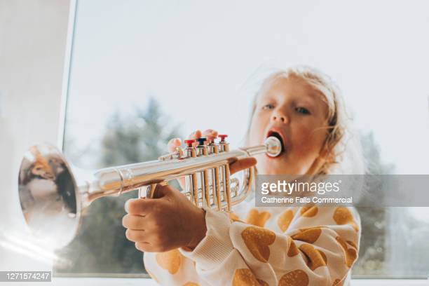 little girl preparing to blow a toy trumpet - wind instrument stock pictures, royalty-free photos & images