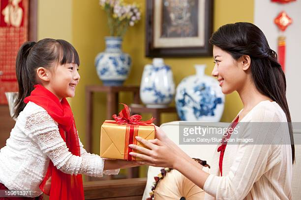 Little girl presenting Chinese New Year gift to mother