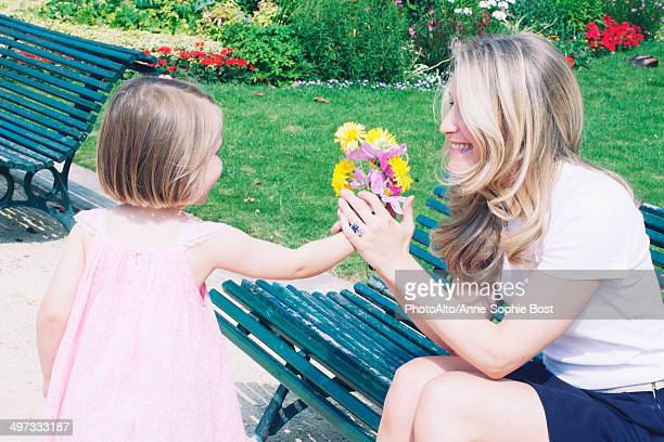 Little girl presenting mother with flower bouquet