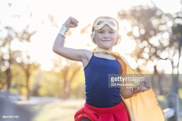 little girl pretends to be strong superhero - superhero stock pictures, royalty-free photos & images