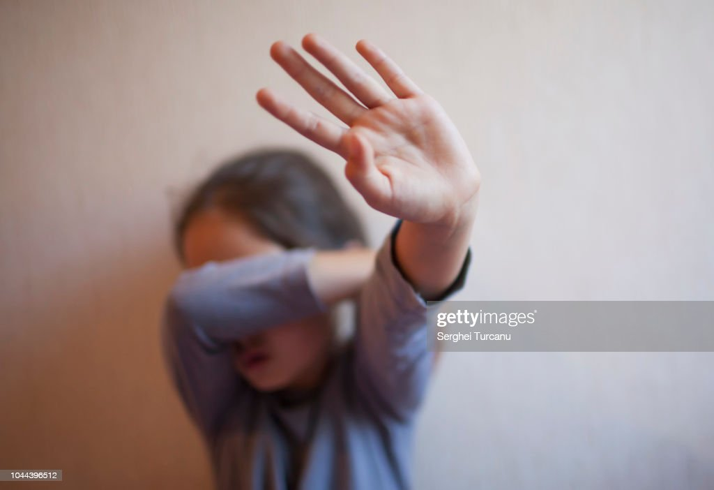 A little girl protects herself with her palm and covers her face : Stock Photo